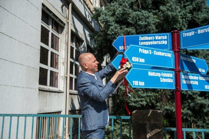 Żoliborz polgármestere felszalagozza az újbudai Polgármesteri Hivatal előtt álló partnervárosi oszlopot
