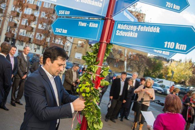 Bilicki Attila polgármester az adai szalagot tűzi fel a partnervárosi oszlopra.